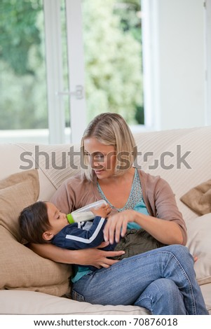 Mother giving a bottle of milk to her son at home - stock photo