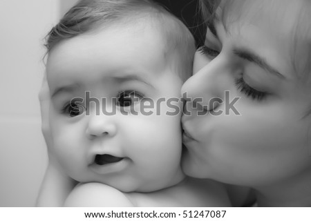 Mother giving a kiss to her little happy baby baby boy; black and white - stock photo