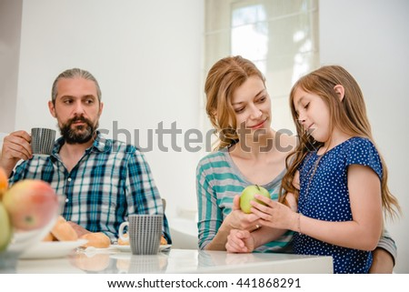 Mother giving apple to her daughter and father is sitting next to her. - stock photo