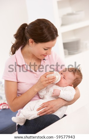 Mother Giving Bottle Baby Boy At Home - stock photo