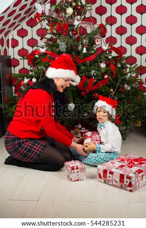 Mother giving Christmas present to her son boy in front of green tree decorated with red and silver baubles