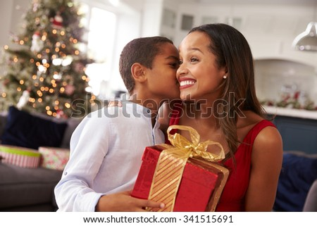 Mother Giving Christmas Presents To Son At Home - stock photo