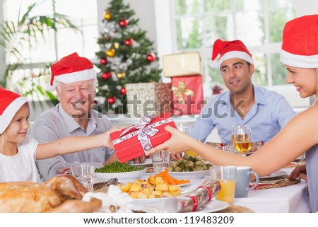 Mother giving daughter christmas present at christmas dinner - stock photo