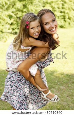 mother giving daughter piggy back ride at summer park - stock photo