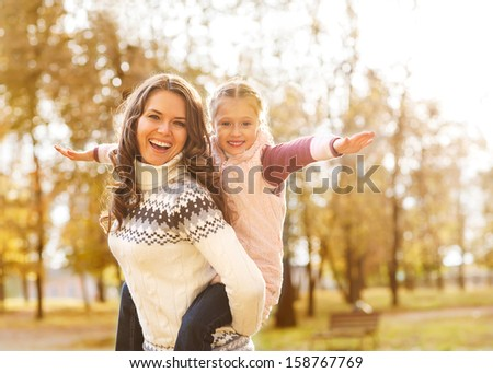 Mother giving daughter piggyback ride in autumn woodland - stock photo