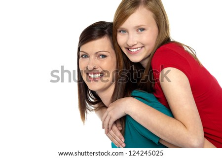 Mother giving daughter ride on back in studio. - stock photo