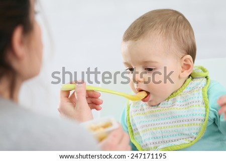 Mother giving fruit sauce to baby boy - stock photo