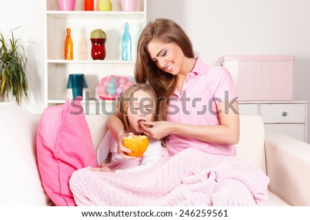 Mother giving fruit to sick child - stock photo