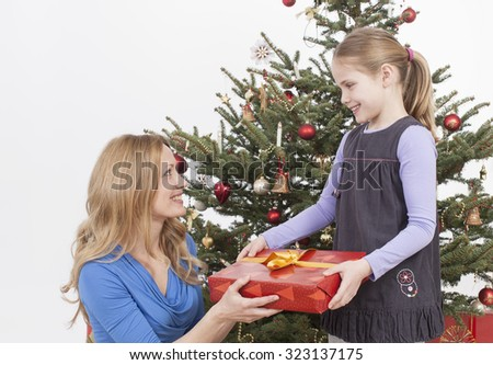 Mother giving gift to daughter, smiling - stock photo
