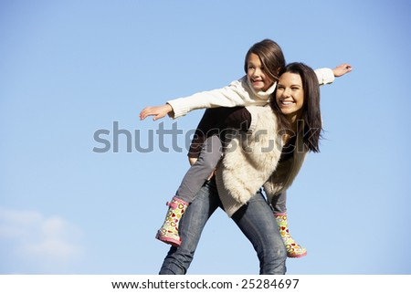 Mother Giving Her Daughter A Piggy Back Ride - stock photo