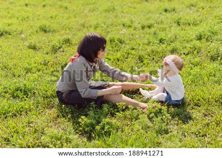 mother giving her daughter dandelion - stock photo