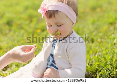 mother giving her daughter flower to smell - stock photo