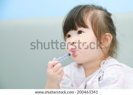 Mother giving her daughter liquid syrup - stock photo