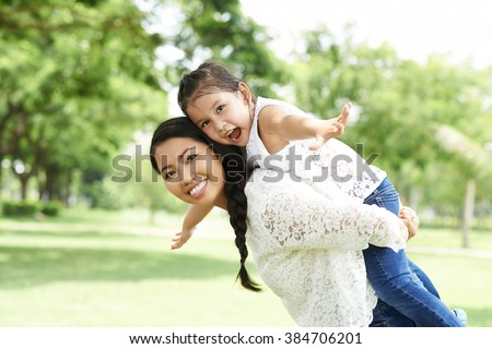 Mother giving her daughter piggyback ride - stock photo