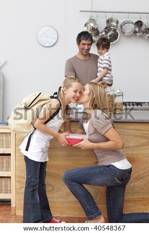 Mother giving her daughter the school lunch and a kiss in the kitchen - stock photo