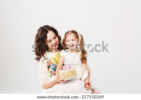 Mother giving her little daughter birthday cake - stock photo