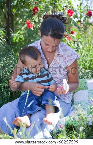 Mother giving homeopathic medicine to her son. Shallow DOF, main focus on their hands switching the tablet. - stock photo