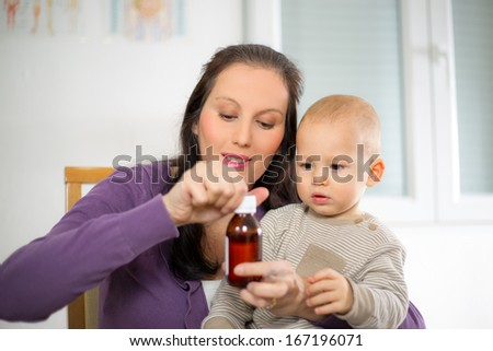Mother giving medicine to baby - stock photo