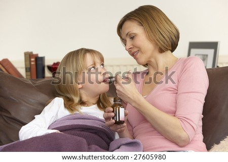 Mother Giving Medicine To Sick Daughter - stock photo