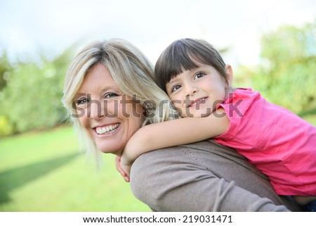 Mother giving piggyback ride to little girl