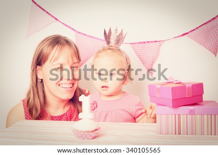 mother giving presents to little daughter on birthday party - stock photo