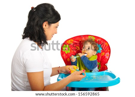 Mother giving puree to her baby boy and having conversation against white background