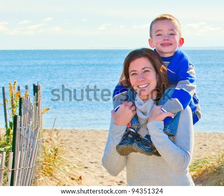 Mother giving son a shoulder ride at the beach