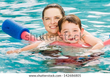 Mother giving son a swimming lesson in pool during summer - stock photo