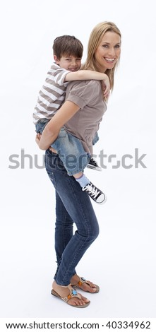 Mother giving son piggy back ride against white background