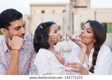 mother giving water to her daughter while father looking at them, portrait of indian family - stock photo