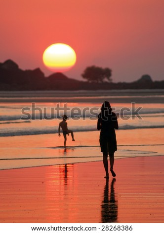 mother goes for a walk with child along a beach on sunset - stock photo