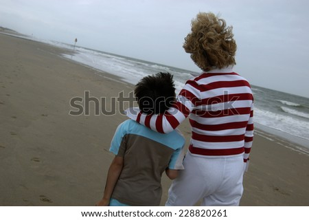 Mother going for a walk with her son at the beach - stock photo