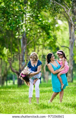 Mother, grandmother and daughters having laugh in the park - stock photo