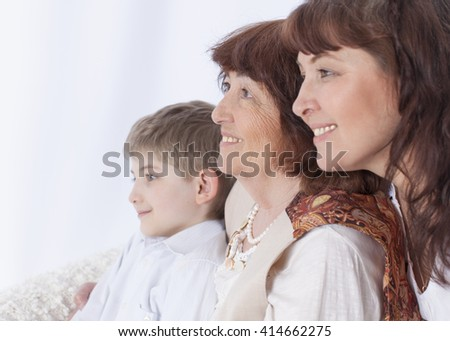 Mother, grandmother and grandson sitting on the couch at home. Looking away and smiling. Horizontal color image. Light background. - stock photo
