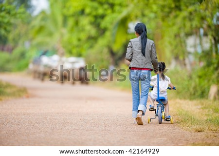 mother guiding her daughter on a bike - stock photo