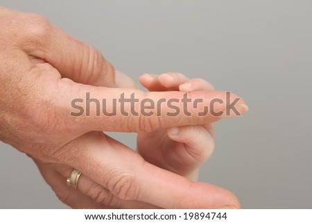mother hand and little baby fingers - stock photo