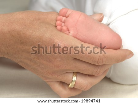 mother hand and little baby foot - stock photo