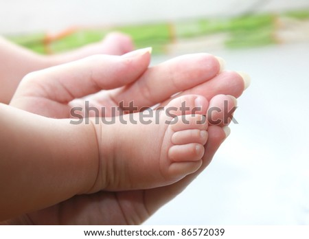 Mother hand holding baby foot. Closeup love family