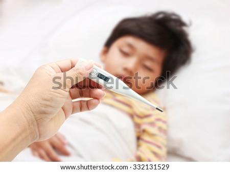 Mother hand holding fever thermometer for a boy ,who has fever sleeping on bed. - stock photo