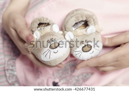 Mother Hand Holding Pink Newborn Baby Booties - stock photo