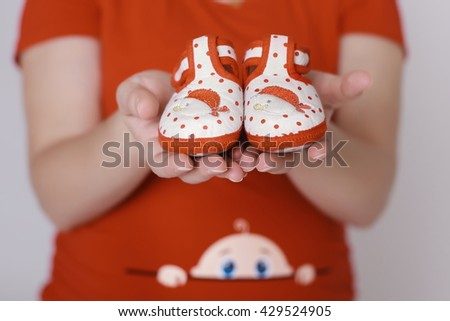 Mother Hand Holding Pink Newborn Baby Booties, New Born Girl - stock photo