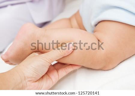 Mother hand massaging leg of her baby - stock photo