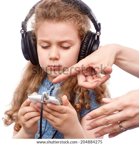 Mother hands showing her daughter to work with smart phone - stock photo