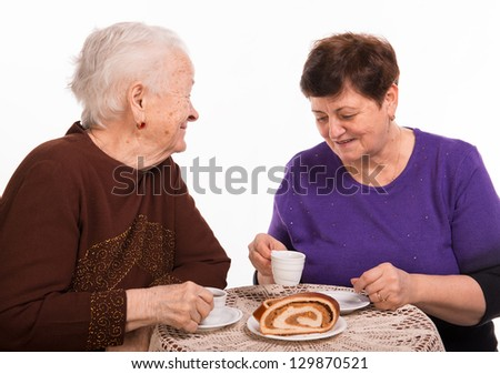 Mother having coffee with her daughter on a white background - stock photo