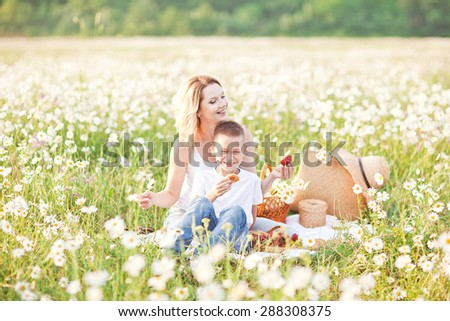 Mother having picnic with his son in the blossom field of camomile in Crimea region