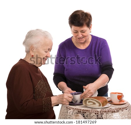 Mother having tea or coffee with her daughter on a white background - stock photo