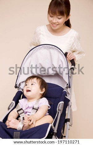 Mother Having The Baby To Sit Down In A Stroller - stock photo