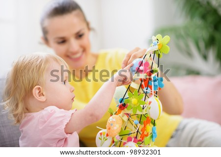 Mother helping baby made Easter decoration - stock photo