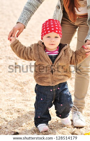 mother helping baby to do first steps - stock photo