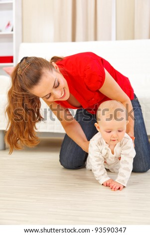 Mother helping cheerful baby learn to creep - stock photo